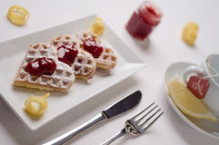 Heart waffles, marmalade, powdered sugar served on rectangular p Royalty Free Stock Photo