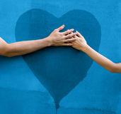 Heart on the wall. Male and female hands touching painted heart on concrete wall royalty free stock photography