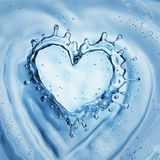 Heart from water splash with bubbles on blue water background Royalty Free Stock Image