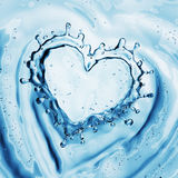 Heart from water splash with bubbles on blue water background Stock Photo