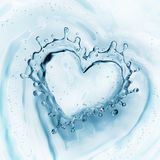 Heart from water splash with bubbles on blue water background Stock Photos