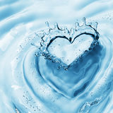 Heart from water splash with bubbles on blue water background Stock Image
