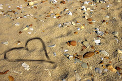 Heart on wet sand Stock Photos