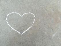 Heart - white chalk hand drawing on black asphalt. Heart - white chalk hand drawing on grey asphalt. summer banner with space for text royalty free stock image