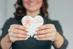 Heart white glazed gingerbread in woman hands, Valentine`s day stock photo