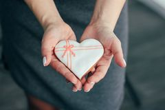 Heart white glazed gingerbread in woman hands, Valentine`s day royalty free stock image