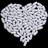 Heart of white oblong tablets Stock Images