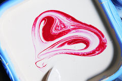 Heart. White oil paint in a blue basin with the red paint stirred as heart Royalty Free Stock Images