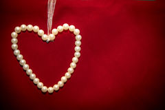 Heart of white pearls on red background Stock Images