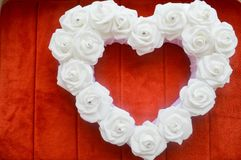 Heart from white roses with rhinestones and diamonds on a red background. Heart of flowers on a background of red carpet Stock Photography