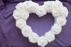 Heart from white roses with rhinestones on a purple background. Stock Image