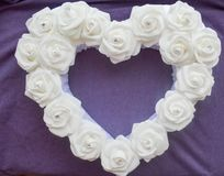 Heart from white roses with rhinestones on a purple background. Royalty Free Stock Photography