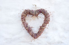Heart on white wall. Rustic heart shape made from twig branches hanging on farmhouse country whitewash brick wall, background for wedding invitation or card Royalty Free Stock Images
