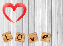 Heart on white wooden background. Love cast out of wooden bricks. Background royalty free stock photo