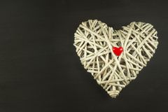 Heart of wicker on wooden background. Symbol of love. Stock Image