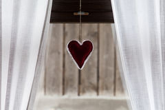 Heart on the window with curtain Royalty Free Stock Photos