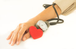 Heart with woman arm checking blood pressure. Royalty Free Stock Photos