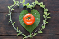 Heart on wood background. Tomato and green leaves on wood background Stock Photography