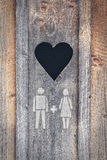 Heart of wood. Heart cut out the wood with painted symbol of man and woman Stock Photo