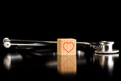Heart Wooden Block in front of Stethoscope Stock Photo