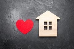 Heart and wooden house on a gray concrete background. The concept of a love nest, the search for new affordable housing for young. Couples and families royalty free stock images