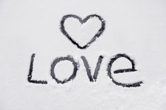 The heart and the word of love. Drawn on a snow-covered glass stock photo