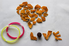 Heart, word Love and two rings. Composition for greeting card: Heart, word Love made from dry orange peel and two rings on a white background Stock Images