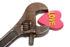Heart in wrench. Plasticine heart with word love in old wrench isolated on white royalty free stock photography