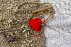 Heart of yarn in cloth and dried flowers on on textile background Stock Images