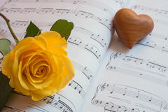 Heart and yellow rose on a sheet of music Royalty Free Stock Image