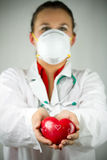 Heart for you. Female doctor in mask holding heart Stock Images