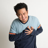 Heartache. Asian male heartache, pressing on chest with painful expression, on plain background Royalty Free Stock Photo