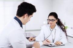 Heartbeat del doctor Checking Patient's imagen de archivo libre de regalías