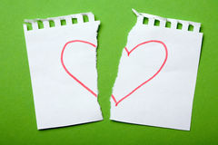 Heartbreak. A conceptual picture of a torn note book page with a heart split in half, depicting heartbreak stock image