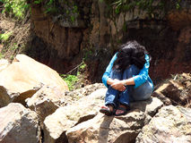 Heartbroken. A heartbroken girl crying while sitting on a rock alone stock photo