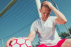Heartbroken Soccer Player. Heartbroken Caucasian Football Player in His 30s with the Ball on the Soccer Field stock images
