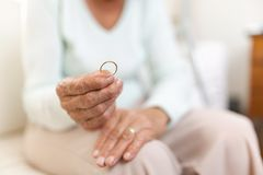 Heartbroken elderly woman holding a wedding ring royalty free stock image