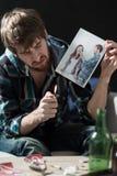 Heartbroken guy destroying love photos. Young desperate heartbroken guy destroying love photos Stock Image