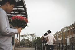 Heartbroken man holding bouquet of red roses feeling sad while s. Asian heartbroken men holding bouquet of red roses feeling sad while seeing women dating with royalty free stock images