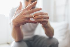 Heartbroken man holding a wedding ring royalty free stock photography