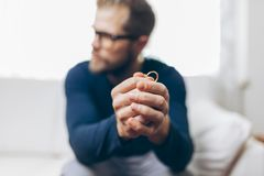 Heartbroken man holding a wedding ring royalty free stock image