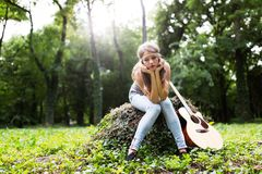 Heartbroken woman in nature with guitar. Battles depression royalty free stock photos