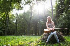 Heartbroken woman in nature with guitar. Battles depression stock photo