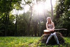 Heartbroken woman in nature with guitar. Battles depression Royalty Free Stock Photo