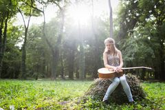 Heartbroken woman in nature with guitar. Battles depression stock images