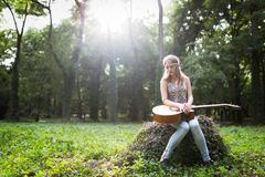 Heartbroken woman in nature with guitar. Battles depression stock image