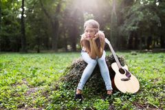 Heartbroken woman in nature with guitar. Battles depression stock photography