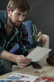 Heartbroken young guy. Drinking beer  and looking on the photos Stock Photography