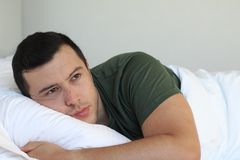 Heartbroken young man laying down in bed.  royalty free stock photos