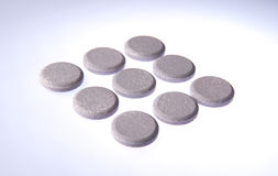 Heartburn Cure Lined Up. A group of antacid pills white graduated background arranged in diamond shape Stock Photography